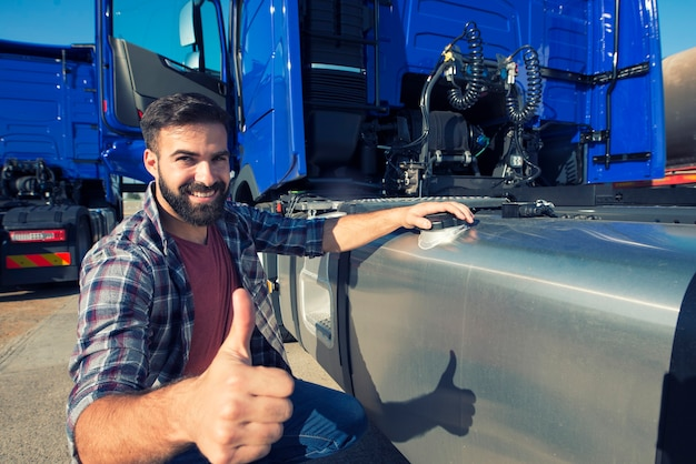 Truck driver opening reservoir tank to refuel the truck and holding thumbs up