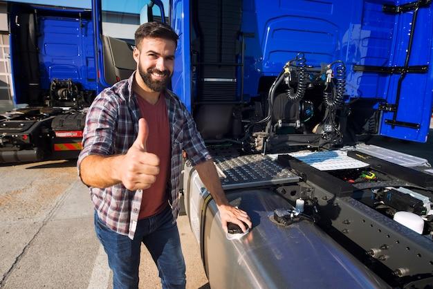 トラックの運転手が貯水タンクを開いてトラックに燃料を補給し、親指を立てる