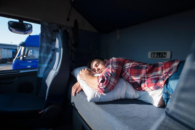 Truck driver sleeping in his cabin after working long routes overtime