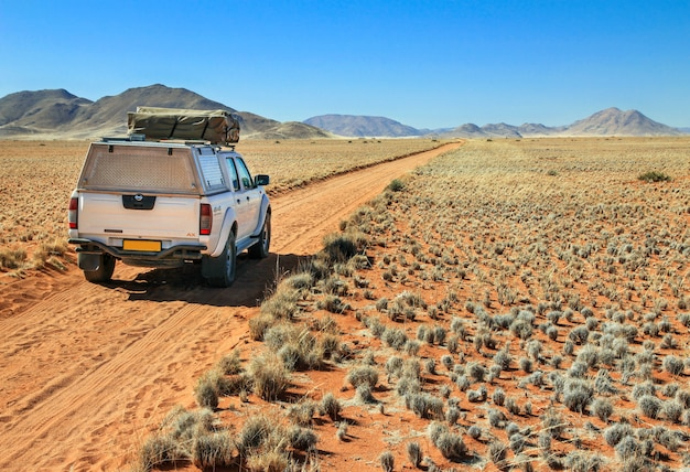 Truck driving on desert road towards the tiras mountains