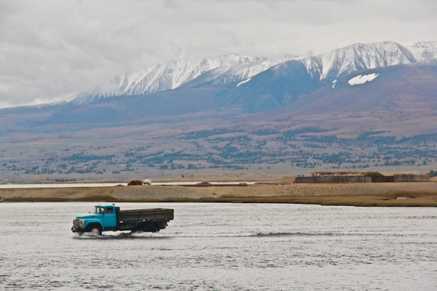 Truck driving in the river surrounded by the mountains covered in snow
