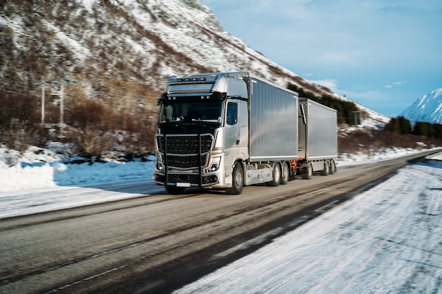 Truck driving on a snowy highway, during a sunny day. winter road safety concept.