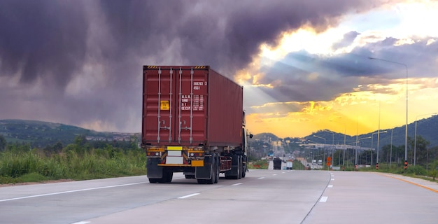 Truck on highway road with red container and sunlight in the back