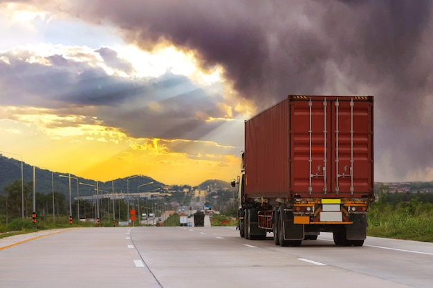 Truck on highway road with red container, transportation concept.,import,export logistic industrial transporting land transport on the expressway with sunrise sky and very cloudy