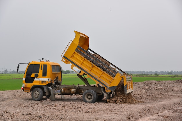 The truck is dumping soil at a construction site
