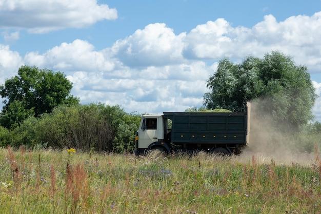 田園地帯でキビを積んだトラックが畑を横切って走っています。