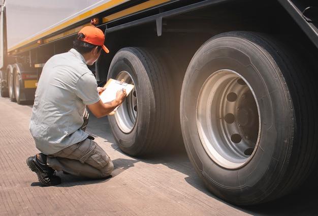 클립보드를 들고 트럭 정비사 드라이버 그의 안전 확인 트럭 바퀴와 타이어