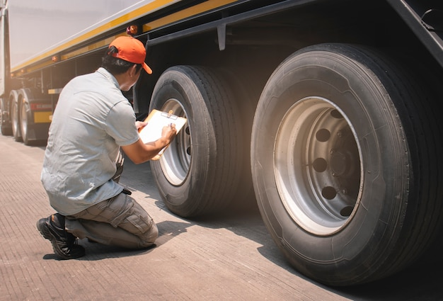 Truck mechanic driver holding clipboard his checking safety a truck wheels and tires