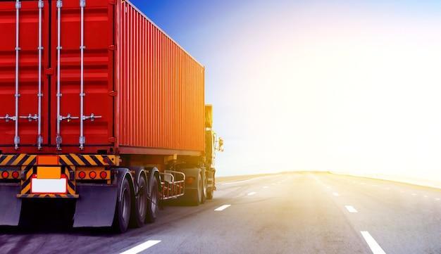 Грузовик на шоссе с красным контейнером, транспортная концепция., импорт, экспорт, логистика, промышленная транспортировка, наземный транспорт на асфальтовой автостраде с голубым небом