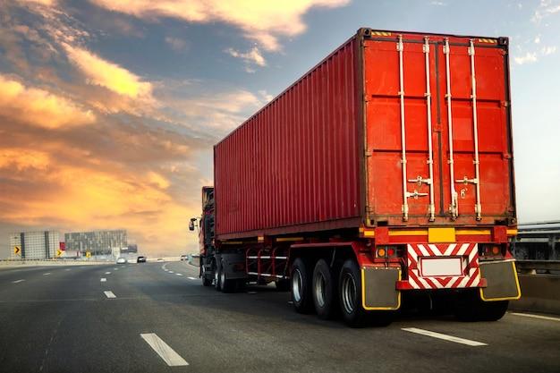 Грузовик на шоссе с красным контейнером, транспортная концепция., импорт, экспорт, логистика, промышленные перевозки
