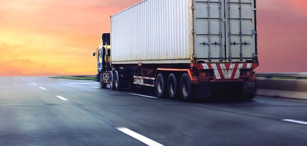 Грузовик на шоссе с белым контейнером, транспортная концепция., импорт, экспорт, логистика, промышленная транспортировка, наземный транспорт на асфальтовой автостраде с восходом солнца