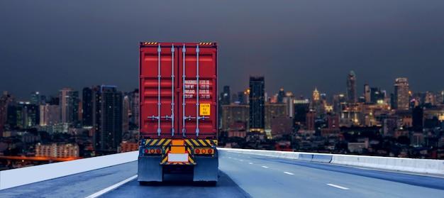 Грузовик на дороге с красным контейнером, концепция транспортировки., импорт, экспорт логистический промышленный транспорт наземный транспорт на скоростной дороге в ночной город