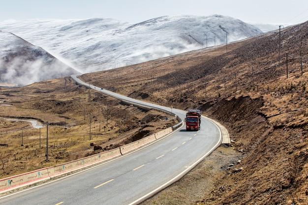 道路上のトラック、雪の山の四川省、中国の下のチベットの美しい冬の道。
