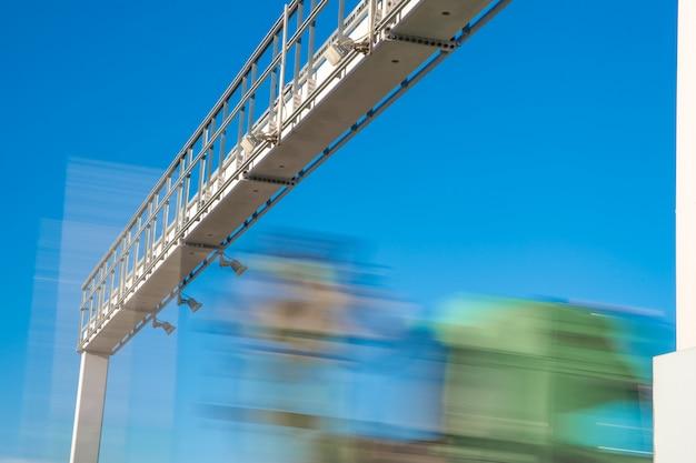 Грузовик проезжает через платные ворота по шоссе платных дорог