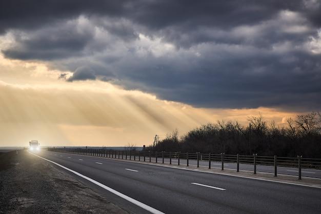 Грузовик едет по асфальтированной дороге на фоне грозовых облаков и лучей солнца
