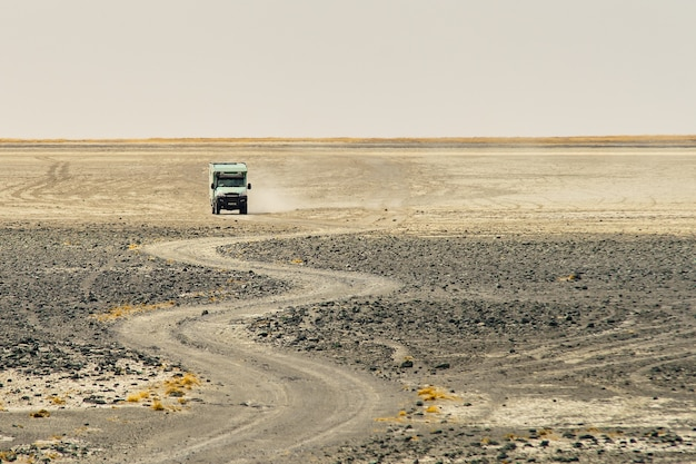 ほこりを作る曲がりくねった岩の多い道を通って乗るトラック