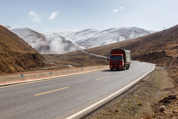 Truck on the road, beautiful winter road in tibet under snow mountain sichuan china