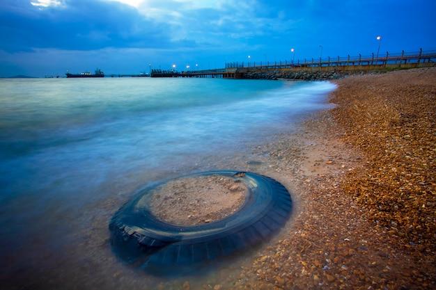 Грузовые шины и морской пейзаж в сумерках