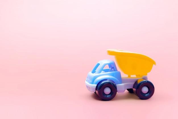 ピンクの背景、テキスト用のスペースにトラックのおもちゃモデル車