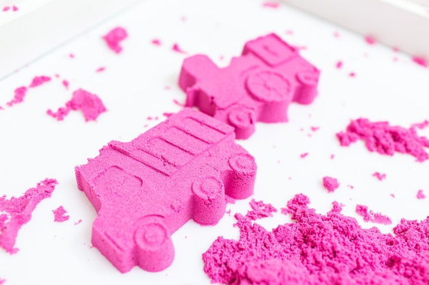 Truck and train made with a pink kinetic sand on a white background.