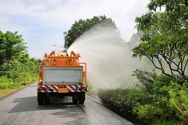 Truck watering a tree by spray water in the park garden.