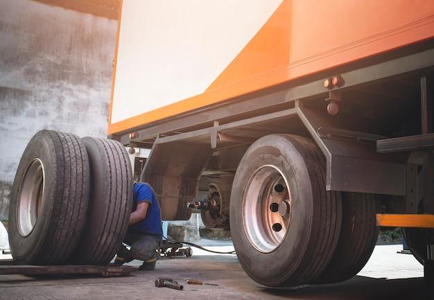 トラックのホイールとタイヤトラックのスペアタイヤタイヤがトレーラーのメンテナンス修理店を変更するのを待っています