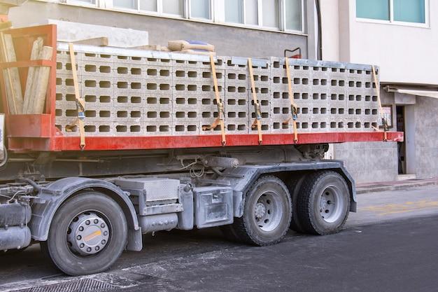 Грузовик с полностью загруженным кузовом из бетонных блоков с цементом.