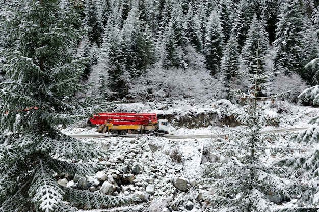 Truck with a crane rides a mountain road, among snow-covered high spruce trees.