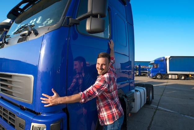 Camionista che abbraccia il suo veicolo camion per il trasporto