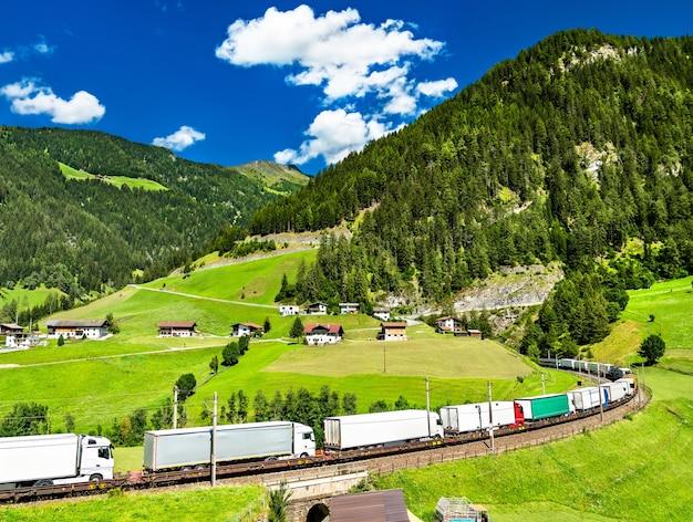 Грузовики пересекают альпы по железной дороге на перевале бреннер в австрии