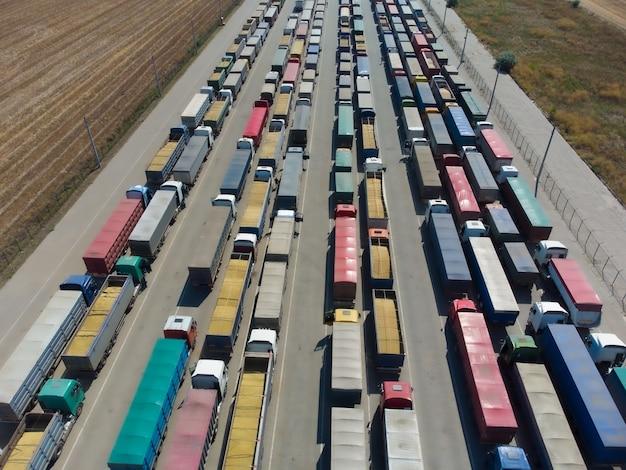 항구의 터미널까지 주차장에 줄지어 있는 트럭들. 하역을 기다리는 트럭이 있는 대형 주차장의 공중 전망. 대형 물류센터. 곡물 제품의 화물 운송.