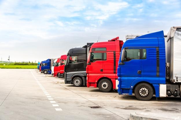 Грузовики на стоянках, грузоперевозки по городам европы. транспорт для доставки грузов по европе