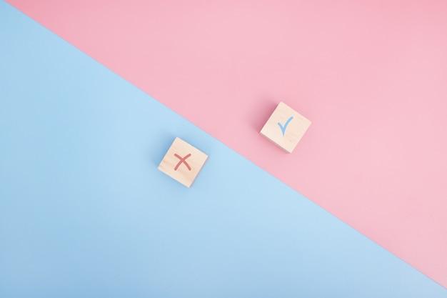 Верный и ложный значок принят отклонен, да или нет на деревянных кубиках. розовый и синий фон.