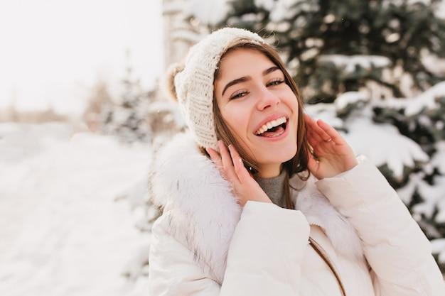 Настоящие яркие эмоции зимней женщины в вязаной шапке, улыбающейся на улице, засыпанной снегом.