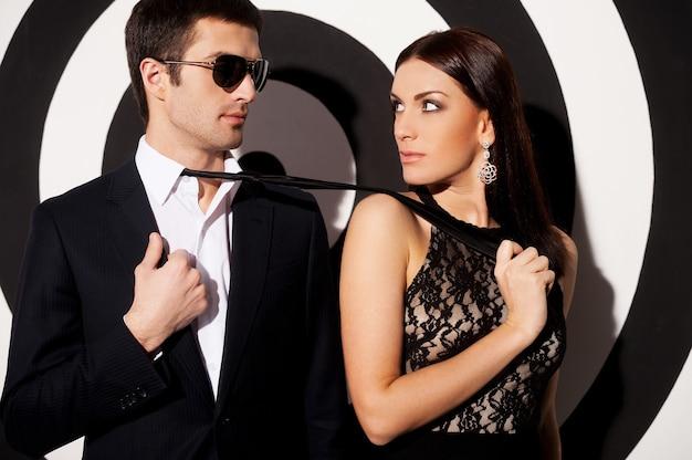 本当の欲望。女性が彼女のボーイフレンドのネクタイをつかんでいる間、黒と白の背景に立っている美しい若い身なりのよいカップル
