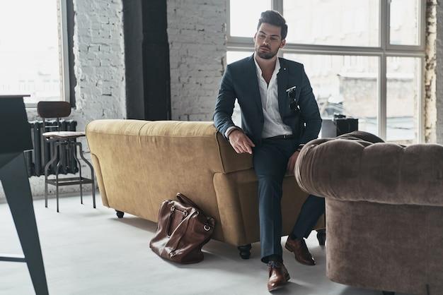 真のエレガンス。ソファに寄りかかって目をそらしている完全なスーツを着た思いやりのある若い男の全長