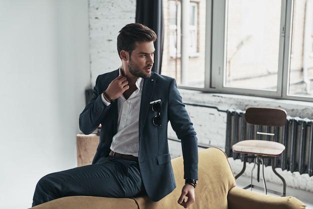 真のエレガンス。フルスーツを着たハンサムな若い男がシャツを調整し、ソファに座って目をそらしている