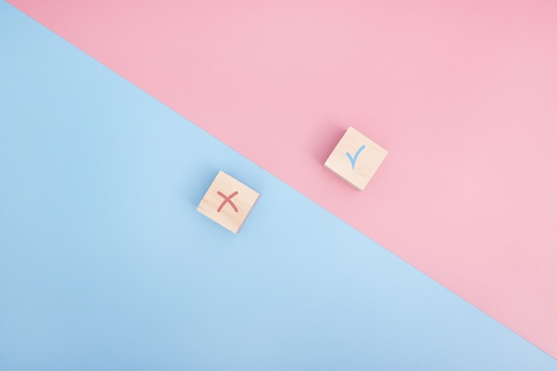 True and false icon accepted rejected, yes or no on wood cubes. pink and blue background.