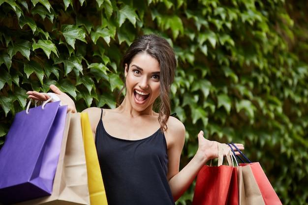本当の女の子の幸せ。興奮した表情でカメラを見て、幸せから悲鳴を上げる、カラフルなバッグを両方の手で大量に保持している黒のドレスで若い美しい黒髪の白人女性