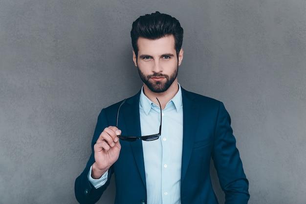 本当にハンサム。彼のサングラスを保持し、灰色の背景に立ってカメラを見ているハンサムな若い男のクローズアップ