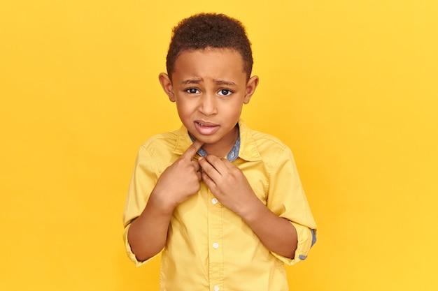 真の人間の反応、感情、感情。人差し指を自分に向けて、怖い顔をしているジャケットの感情的なおびえた就学前の男の子