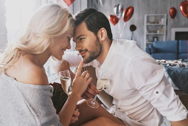 Искренняя любовь. красивая молодая пара пьет шампанское и улыбается, сидя лицом к лицу в спальне