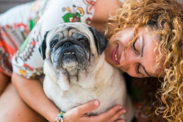 美しい白人女性と老犬のパグ、奇妙な友人と家族の代替概念の間の真の愛。陽気な女性と笑顔の家畜。肖像画
