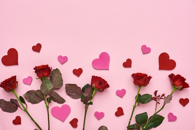 True love red roses with decorative paper hearts on pink background
