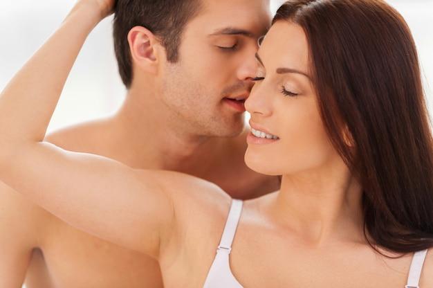 真の情熱。彼のガールフレンドにキスするハンサムな若い上半身裸の男