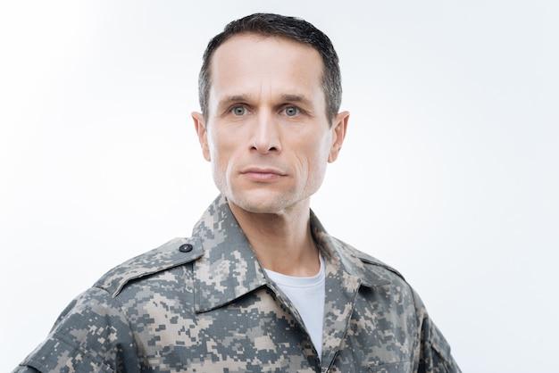 Истинный патриот. серьезный хороший умный военнослужащий стоит на белом фоне и думает о своей стране, выполняя свои обязанности