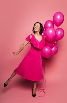 Настоящая принцесса. фотография в полный рост обрадованной девушки в платье цвета фуксии, которая стоит на левой ноге и держит в левой руке букет воздушных шаров.