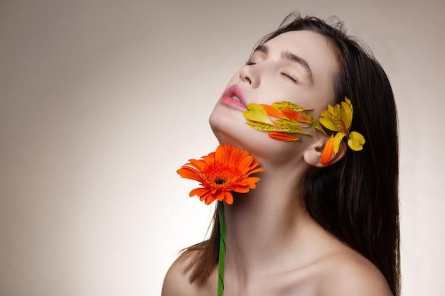 真の満足。花でポーズをとっている間真の満足を得ている暗い髪の細いモデル
