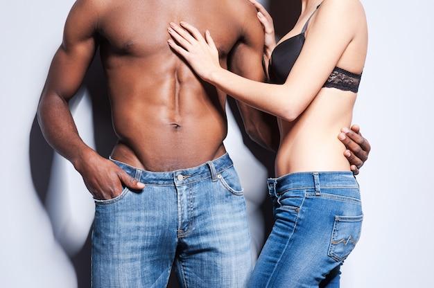 真の官能性。両方が灰色の背景に立っている間、互いに結合しているジーンズの美しい若いカップルのクローズアップ