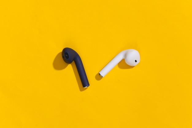 明るい黄色の背景に真のワイヤレスbluetoothヘッドフォンまたはイヤフォン。